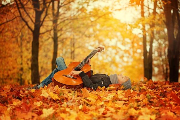 秋の晴れた日に草の上に横たわって、ギターとかわいい男の子 Premium写真
