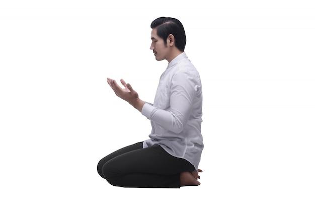 祈りながら座っている宗教的なアジアのイスラム教徒の男性 Premium写真