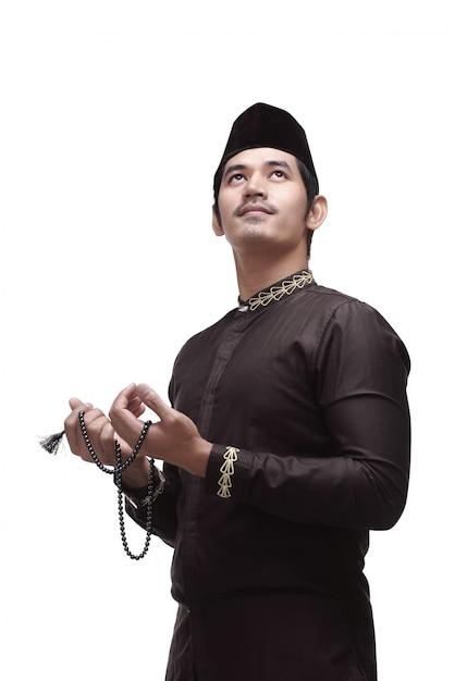 伝統的な衣装で祈っている宗教的なアジアのイスラム教徒の男性 Premium写真