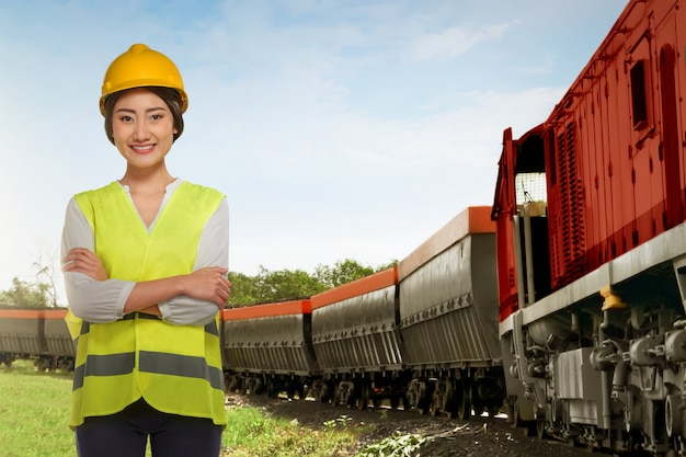貨物列車の横に立っている美しいアジア鉄道従業員女性 Premium写真