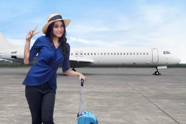 Усмехаясь азиатская женщина с положением чемодана Premium Фотографии