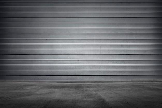 コンクリートの床と金属製のローラーシャッターの質感 Premium写真
