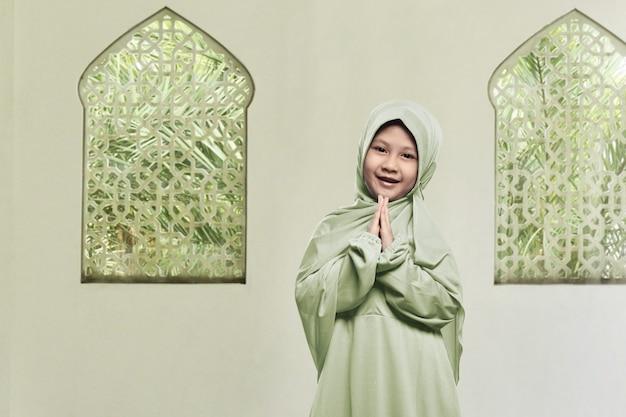 ヒジャーブの祈りを着ている陽気なアジアのイスラム教徒の少女 Premium写真