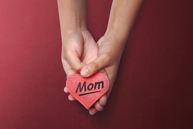 母の日メッセージと赤いハートを持っている人の手 Premium写真