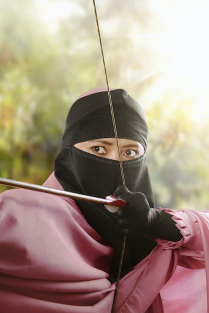 矢印を撮影する準備ができての弓でアジアのイスラム教徒の女性を閉じる Premium写真