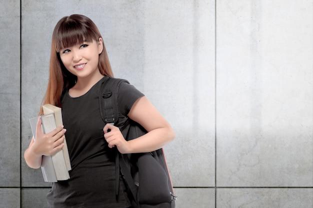 本を持つかなりアジア大学生女性 Premium写真