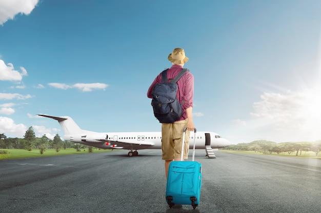 飛行機にスーツケースを持って歩くアジア旅行者の男の背面図 Premium写真