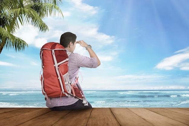 アジアの若い観光客に座っていると海の景色を見て Premium写真