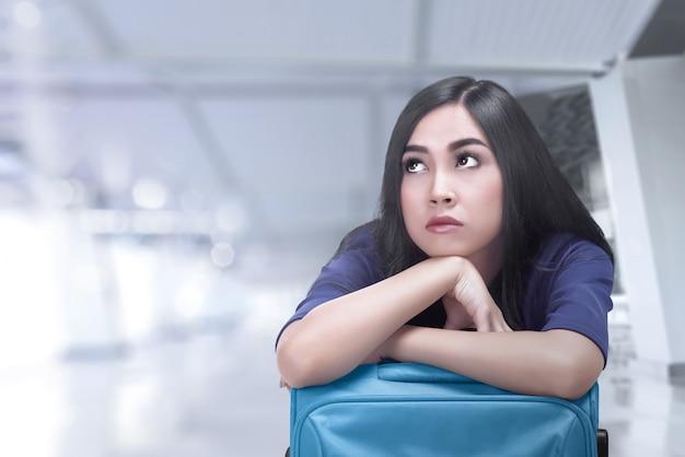 彼女の飛行を待っているスーツケースと退屈のアジア旅行者女性 Premium写真
