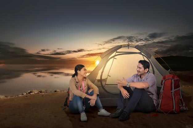 Счастливый азиатский путешественник пар с шатром наслаждаясь временем захода солнца Premium Фотографии