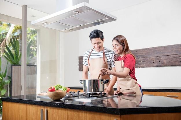 Веселая азиатская пара готовит вместе Premium Фотографии