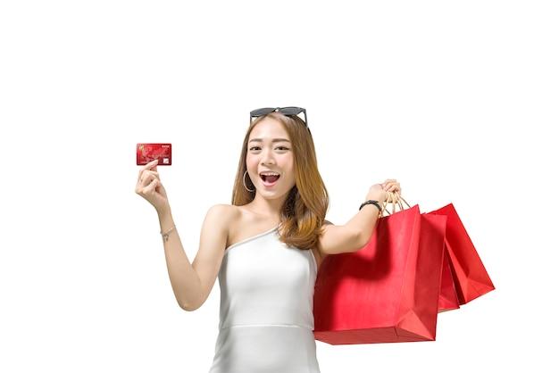 Довольно азиатская женщина с красными бумажными сумками показывая ее кредитную карточку Premium Фотографии