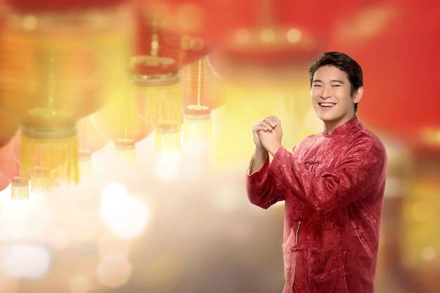 提灯をぶら下げと立っているチャイナスーツの若い中国人男性 Premium写真