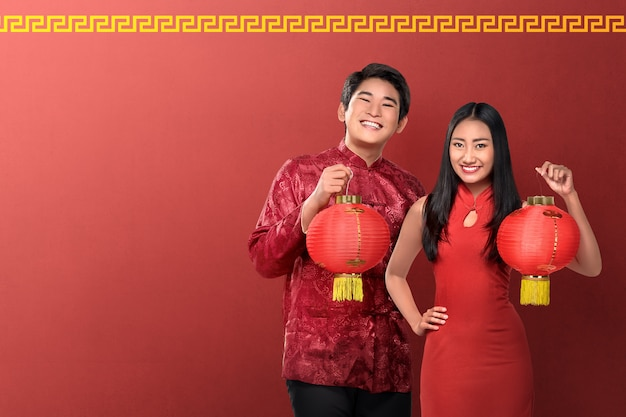 Красивая китайская пара держит красные фонари на красном фоне Premium Фотографии