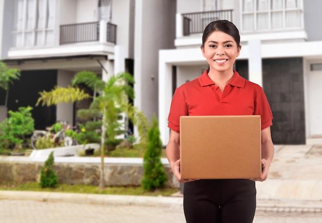 パッケージを提供する若いアジアの宅配便の女性 Premium写真