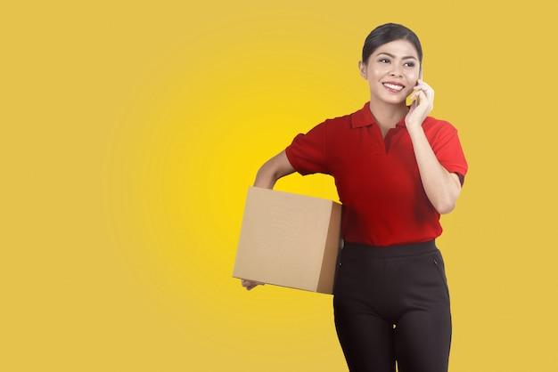 小包を押しながら携帯電話を使用してかなりアジアの女性の宅配便 Premium写真