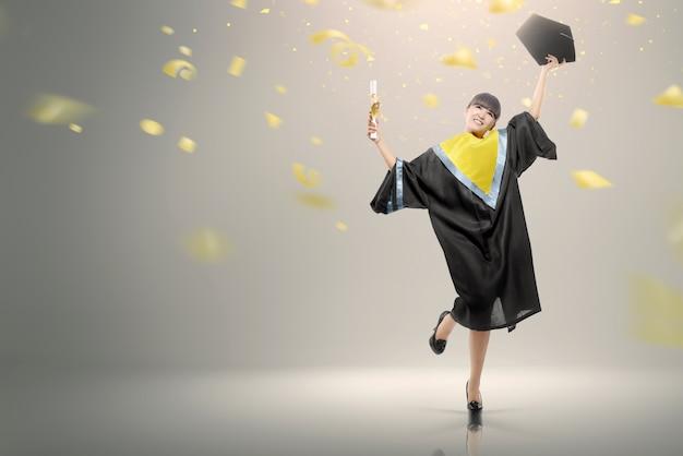 彼女の卒業を祝うスクロールを持つ若いアジア女性 Premium写真