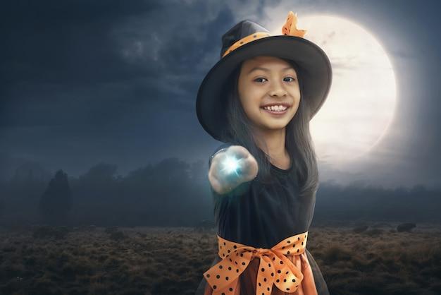 Усмехаясь азиатская девушка ребенка используя ее волшебную силу Premium Фотографии