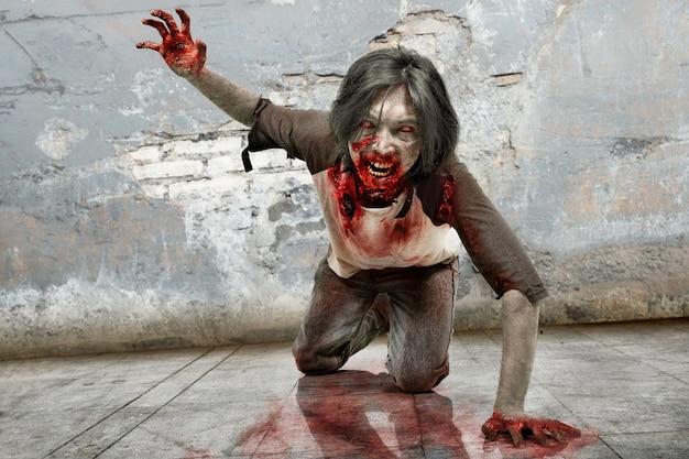 クロール血の口を持つ怒っているゾンビ男 Premium写真
