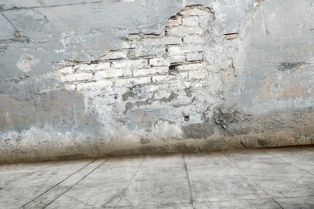 汚れた床と台無しにレンガの壁 Premium写真