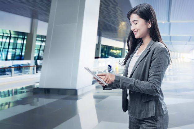 デジタルタブレットを使用して笑顔のアジアビジネス女性 Premium写真