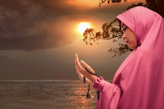 美しいアジアのイスラム教徒の女性が祈りビーズで祈る Premium写真
