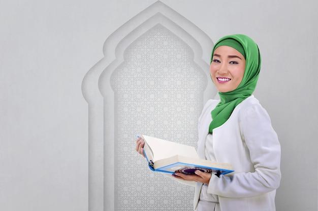 美しいアジアのイスラム教徒の女性はコーランを読む Premium写真