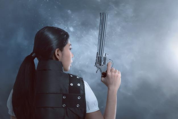Вид сзади азиатской женщины с полицейской форме проведения оружия Premium Фотографии
