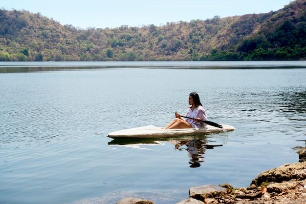 アジアの女性がサトンダ島の湖でカヤックを漕ぐ Premium写真
