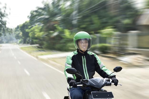 Молодой человек работает мотоциклистом Premium Фотографии