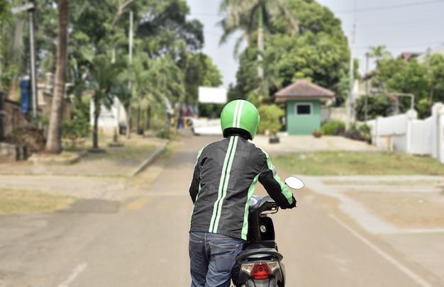 Вид сзади мотоцикла водитель такси, толкая его мотоцикл Premium Фотографии