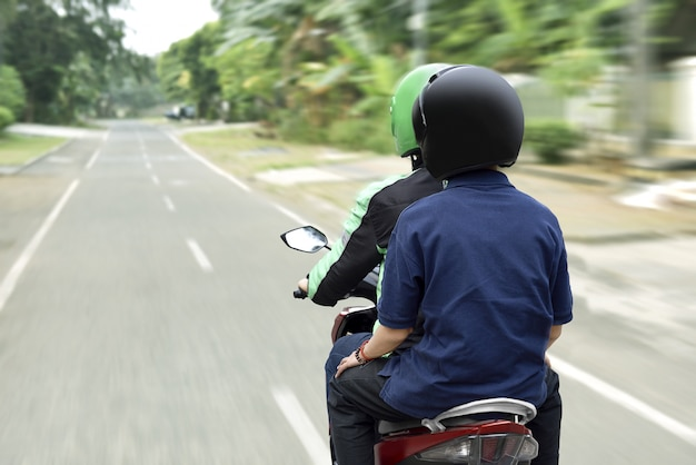 彼の目的地に乗客を配達するオートバイのタクシー運転手の肖像画 Premium写真