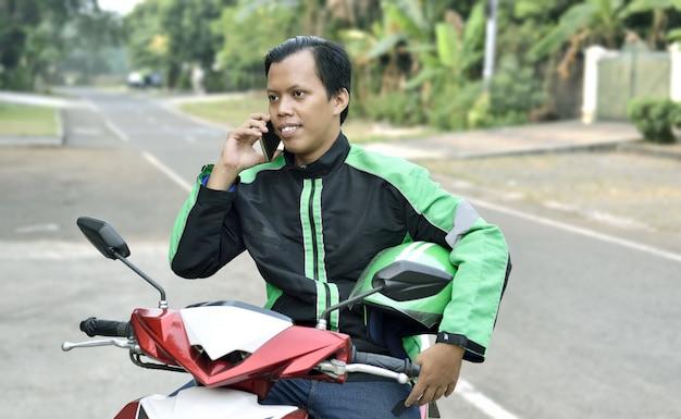 Азиатский мотоцикл такси человек с помощью телефона Premium Фотографии