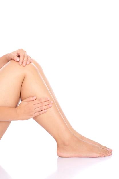 膝のけが。白い背景で隔離された彼女の足を保持している女性 Premium写真