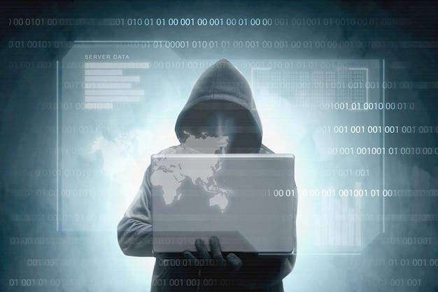 Хакер в черном балахоне держит ноутбук с виртуальным дисплеем данных сервера, гистограммой, двоичным кодом и картой мира Premium Фотографии