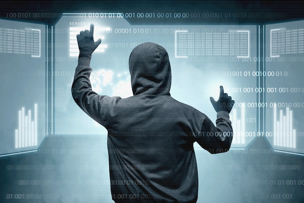 仮想画面に触れる黒いパーカーのハッカーの背面図 Premium写真