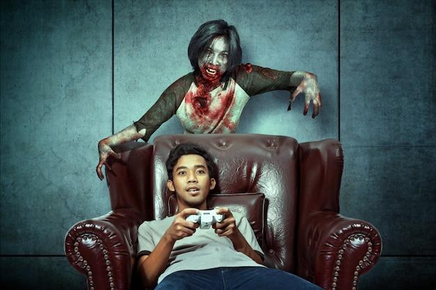 ソファでゲームをしているときに怖いゾンビがアジアの男性に出没しました Premium写真