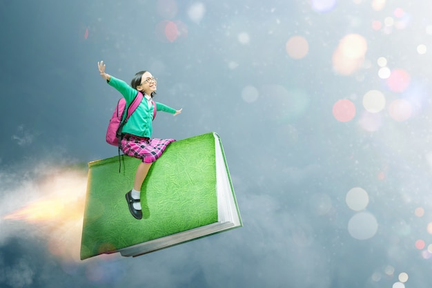 メガネと本の上に座ってバックパックとアジアのかわいい女の子 Premium写真