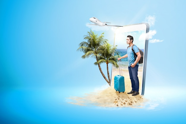 Азиатский мужчина с чемоданом и рюкзаком, стоя на пляже Premium Фотографии