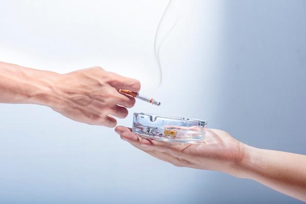 男の手は、喫煙者に透明な灰皿を与える Premium写真