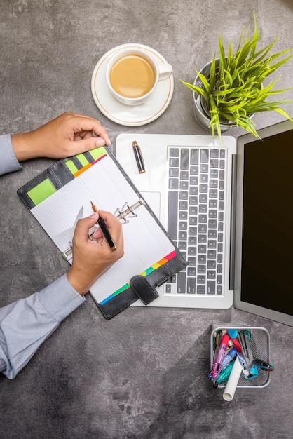 ノート、コーヒー、鉢植え、ビジネスアクセサリーとメモ帳で書くビジネスマンのトップビュー Premium写真