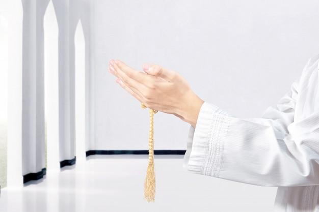 彼の手に数珠で祈るイスラム教徒の男性 Premium写真