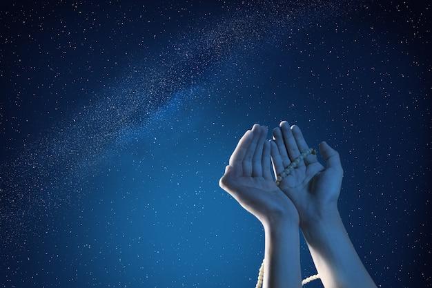 屋外で数珠で祈るイスラム教徒の手 Premium写真