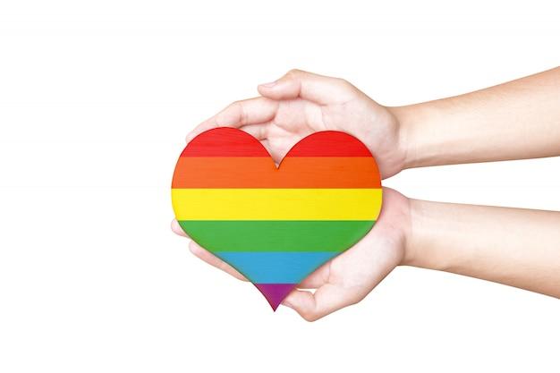Человеческие руки держат сердце с радужным флагом как символ лгбт Premium Фотографии