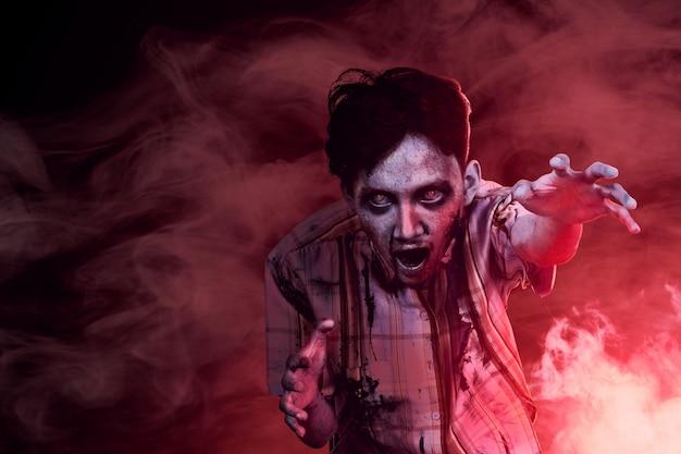 血と暗い霧の中で歩く彼の体に傷を付けた恐ろしいゾンビ Premium写真