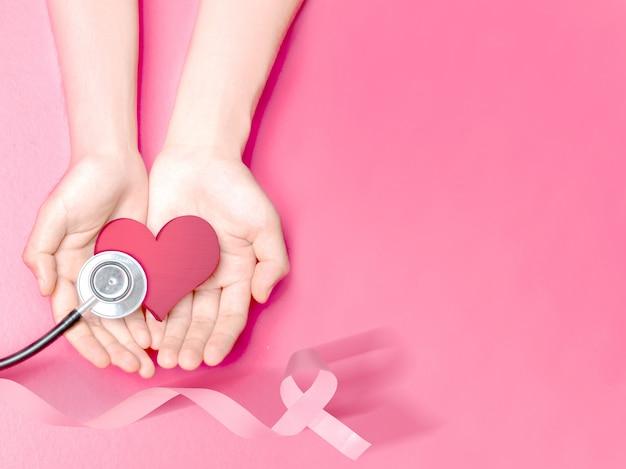Человеческие руки, показывая розовое сердце и стетоскоп с розовой лентой Premium Фотографии
