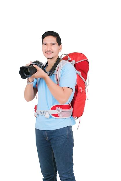 写真を撮るカメラを持ってバックパックを持つアジア人 Premium写真
