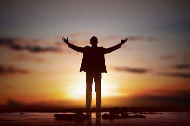 ビジネスマンのシルエットが手を上げ、神に祈る Premium写真