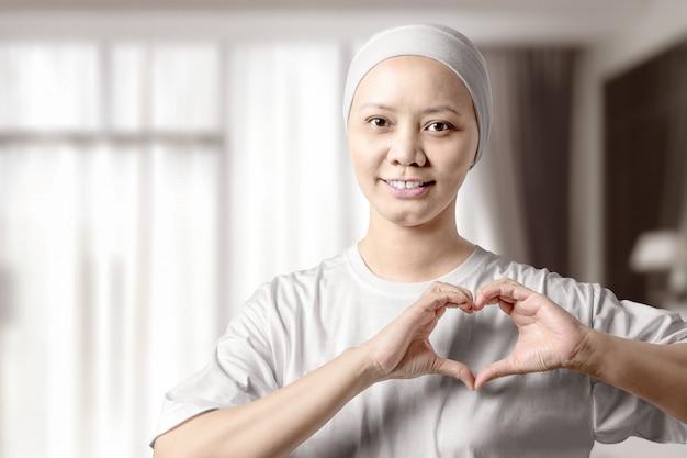 Азиатская женщина в белой рубашке показывая знак сердца с ее руками на доме Premium Фотографии