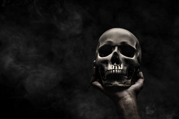 人間の頭蓋骨を持っている手 Premium写真